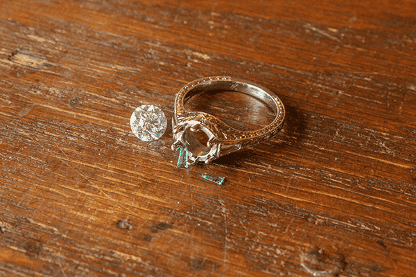 Custom Emerald Accented Engagement Ring Standing with Diamond on Wood